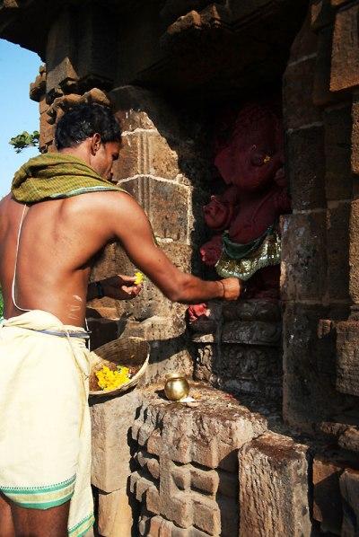 Kapłan w jednej z licznych świątyń w regionie Orissa przystraja figurkę Ganeshy nagietkami, fot. Paweł Wroński