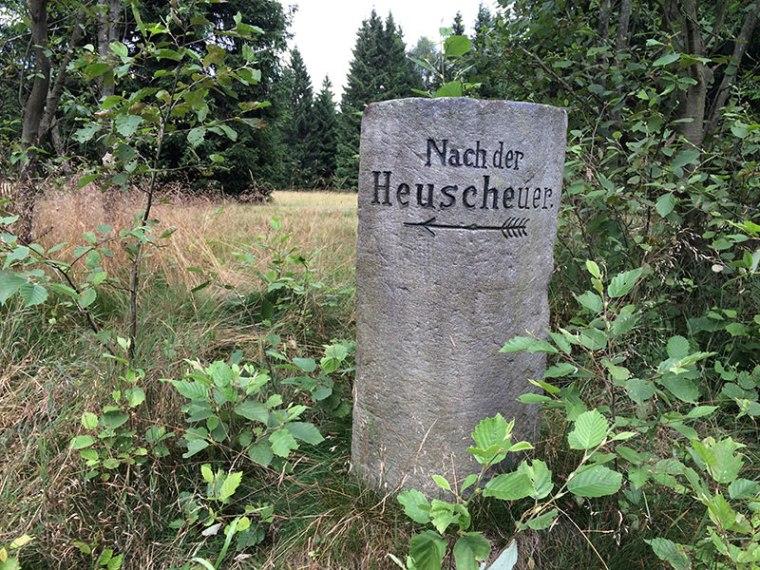 """Dolny Śląsk był przez stulecia jednym z krajów związkowych Niemiec. Nic więc dziwnego, że w wielu miejscach spotykamy pamiątki niemieckiej przeszłości. Takie choćby jak ten drogowskaz z napisem """"Na Heuscheuer"""", fot. Paweł Wroński"""