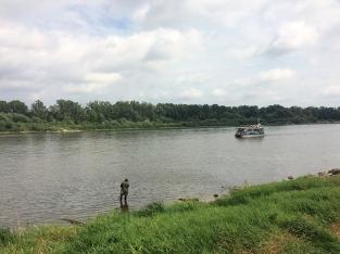 Wędkarz nad Wisłą, tramwaj wodny i łęgi na prawym brzegu rzeki, fot. Paweł Wroński